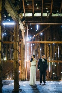 bride and groom hold hands in a barn at armstrong farms